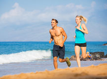 Couple running on beach. Athletic attractive couple running on beach Royalty Free Stock Photos