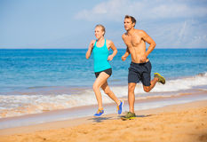 Couple running on beach. Athletic attractive couple running on beach Stock Photos