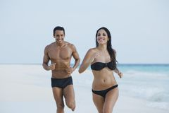 Couple running on the beach. Couple running and enyoing on the beach daytime Royalty Free Stock Photography