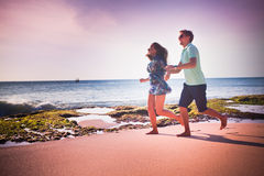 Couple running at the beach. Happy couple running at the beach Royalty Free Stock Photo