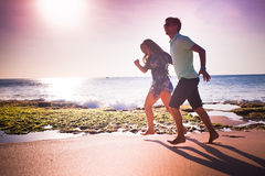 Couple running at the beach. Happy couple running at the beach Royalty Free Stock Images