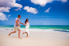 Couple running at the beach. Happy couple running at the beach Stock Photos
