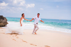 Couple running at the beach. Happy couple running at the beach Royalty Free Stock Image