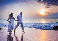 Couple running at the beach. Happy couple running at the beach Stock Image