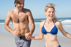 Couple running at beach. Happy young couple running at beach while holding hands. Portrait of a joyful couple in summer vacation. Newly wed couple enjoying at Stock Photo