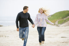 Couple running at beach holding hands. Smiling Stock Photos