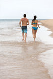 Couple running beach Stock Images