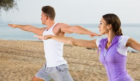 Couple running on beach by sea. At daytime Royalty Free Stock Photo