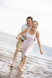 Couple running at the beach smiling.  Royalty Free Stock Photo
