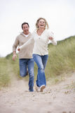 Couple running at beach smiling Stock Photos