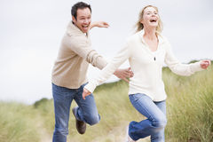 Couple running at beach smiling.  Royalty Free Stock Photography