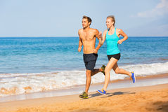 Couple running on the beach Stock Photos