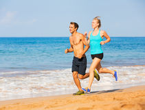 Couple running on the beach Stock Image