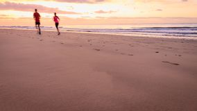 Couple are running on the beach at sunrise.  Royalty Free Stock Image