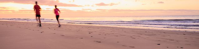 Couple are running on the beach at sunrise. Banner photography format Royalty Free Stock Photo