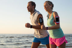 Couple running on the beach during sunset with their headphones plugged in. Two  running on the beach during sunset with their headphones plugged in Stock Images