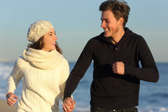 Couple running on the beach in winter. Happy couple running on the beach in winter with the sea in the background Royalty Free Stock Photography