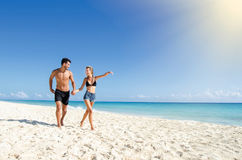 Couple running at the beach. Young couple running at the beach Royalty Free Stock Images