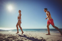 Couple running on beach. Young couple running on beach on a sunny day Royalty Free Stock Images