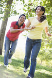 Couple running and being playful outdoors smiling Royalty Free Stock Photos