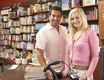 Couple running bookshop. Stood behind the counter smiling Stock Images