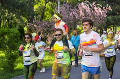 Couple running with children. Couple running with their two children on their shoulders and covered in colored powder at the Color Run event on April 26 in Royalty Free Stock Images