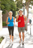 Couple running on city street Royalty Free Stock Photography