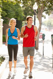 Couple running on city street Stock Photography