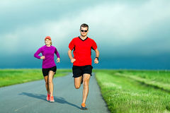 Couple running on country road Stock Image