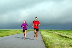 Couple running on country road Royalty Free Stock Image