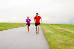 Couple running on country road. Man and women two people runners running on country road, healthy fitness lifestyle, sport speed training beautiful landscape Stock Image