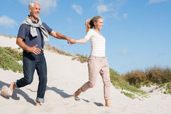 Couple running down dune Royalty Free Stock Image