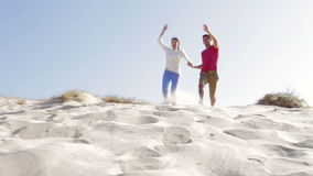 Couple Running Down Sand Dune Together. Couple in casual clothing running down sand dune towards camera position. Shot on Canon 5d Mk2 with a frame rate of 30fps stock video footage
