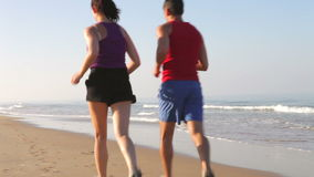 Couple Running On Empty Beach. Couple in sportswear running along empty beach past camera position and into distance. Shot on Canon 5d Mk2 with a frame rate of stock video