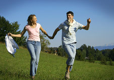 Couple running in a field Royalty Free Stock Photography