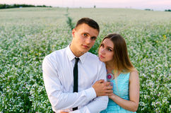 Couple running in field holding hands. Stock Image