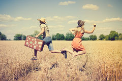 Couple running in field, man holding in his hand vintage suitcase on countryside landscape blue sky outdoors background Stock Photo