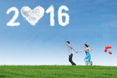 Couple running at field with numbers 2016 Stock Images