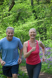 Couple running in forest with bluebell flowers Royalty Free Stock Photography