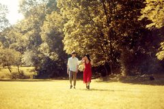 Couple running in the forest , field. Girl in a long red dress and hat, stylishly dressed man. Sunset in the park. The girl royalty free stock images