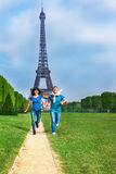 Couple running in front of the Eiffel Tower Royalty Free Stock Photos