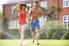 Couple Running Through Garden Sprinkler. Having Fun royalty free stock images