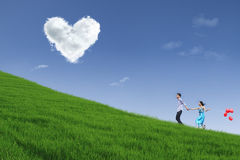 Couple running on hill with heart cloud Stock Photography