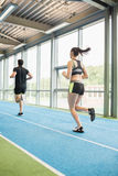 Couple running on the indoor track Royalty Free Stock Image