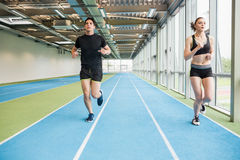 Couple running on the indoor track Stock Image