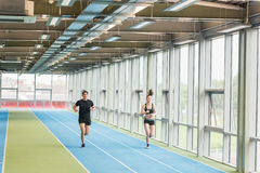 Couple running on the indoor track Royalty Free Stock Photos