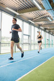 Couple running on the indoor track Royalty Free Stock Images