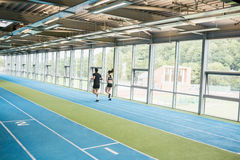 Couple running on the indoor track Stock Images