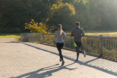 Couple running or jogging outdoors Stock Photos