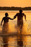 Couple running in lake. Couple at sunset run in the lake Royalty Free Stock Photo
